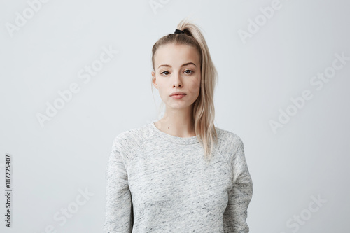 Fotografie, Obraz  Attractive beautiful female with blonde pony tail, feeling self-assuarance while posing against blank studio wall