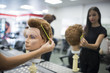 Hairdressers training with maniqui heads in barber shop school