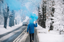 Person With Blue Bengal On The Winter Snowy Road