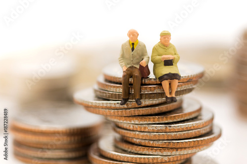Fototapeta Miniature people, Old couple figure sitting on top of stack coins using as background retirement planning, Life insurance concept. obraz