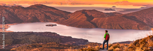 Poster Deep brown Travel hiking man looking at nature landscape sunset panoramic banner background. Adventure traveler in outdoor New Zealand, backpacking hiker. Copy space panorama.
