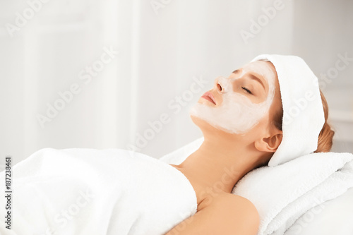 Photo  Beautiful young woman with facial mask in spa salon