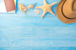 top view of hat and sea shell on light blue wood plank floor for summer vacation time background