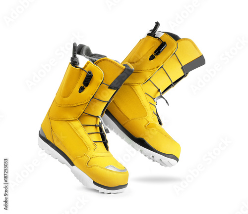 Technological yellow snowboard boots on white background