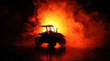 Silhouette Of Tractor At Night With Dark Foggy Background. Toned. Burning Vehicle.