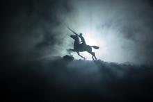 World War Officer (or Warrior) Rider On Horse With A Sword Ready To Fight And Soldiers On A Dark Foggy Toned Background. Battle Scene Battlefield Of Fighting Soldiers. War Scene.