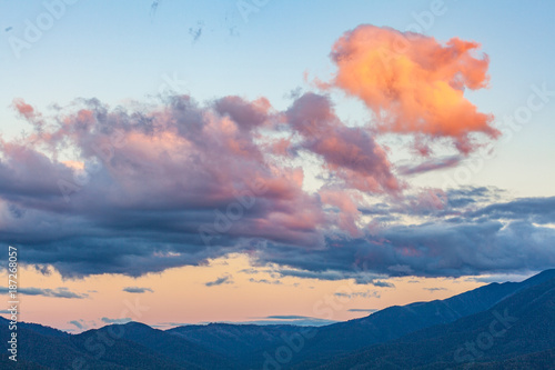 Clouds glowing in orange sunset light over mountains #187268057
