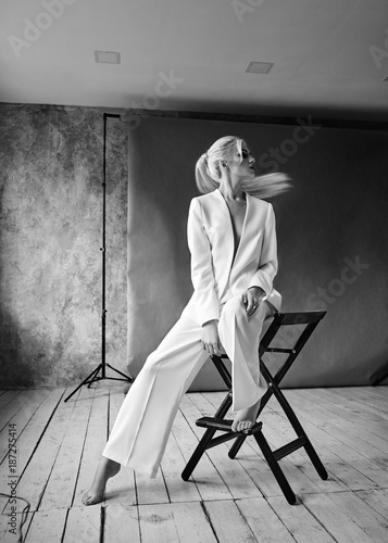 High Fashion blond woman in white suit. Elegant Style model. Dynamic shot in Photo studio shooting Wall mural