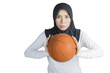 Muslim woman posing with a basketball