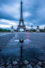 A Reflection Of The Eiffel Tower In A Puddle On The Street In Paris