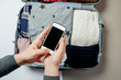 Woman hands with phone on the background of Open suitcase packed with clothes. Winter vacations and holidays. Top view