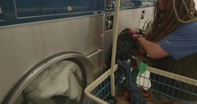 Man With Dreads Putting Clothes Into A Dryer At Laundromat