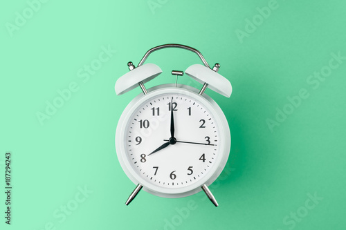 Stampa su Tela vintage alarm clock on the middle of solid light green color background