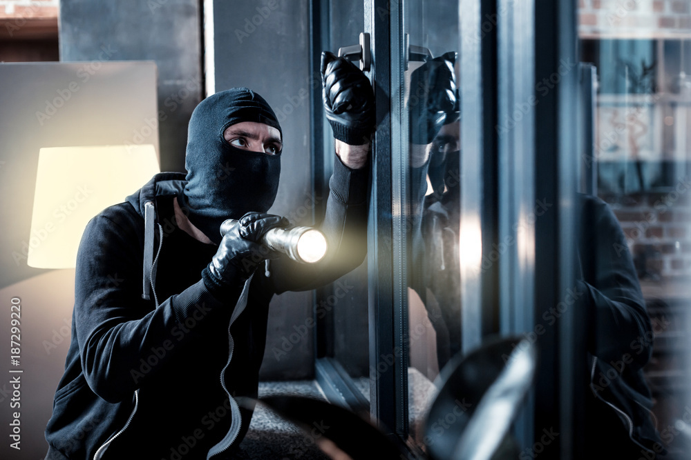 Fototapeta Burglary. Skilful professional masked burglar opening a window and holding a torch and breaking into the house