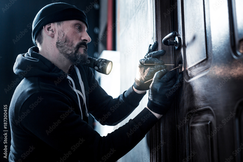 Fototapeta Unlocking. Serious professional bearded robber holding a torch and wearing gloves and unlocking the door