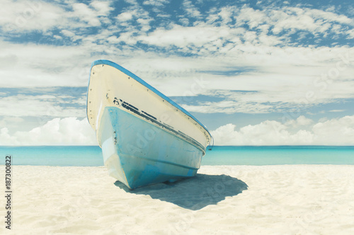 Old shabby boat ashore on sandy beach near sea, cloudy sky Canvas Print