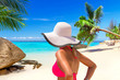 Beautiful woman in white hat on the tropical beach