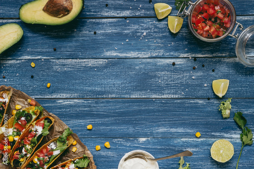 Mexican tacos with salsa and avocado on the wooden blue background, top view