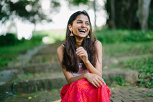 Young Indian Lady In A Summer Dress Laughing In A Park