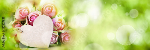 Roses with greeting card on spring background
