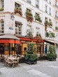 canvas print picture - Typical view of the Parisian street with tables of brasserie (cafe) in Paris, France