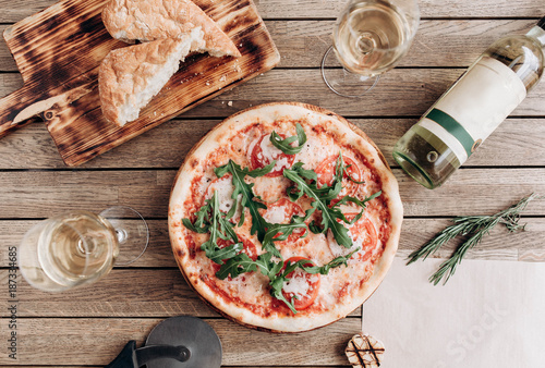 Italian pizza margherita with arugula, with a bottle and two glasses of white wine on a wooden table