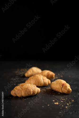 several whole croissants with crumbs on a dark background