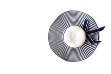Sun Hat On White Isolate Background. Top View With Copy Space. White And Navy Blue Color Striped And Bow.