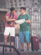Two friends with suitcases are walking with map and photographin
