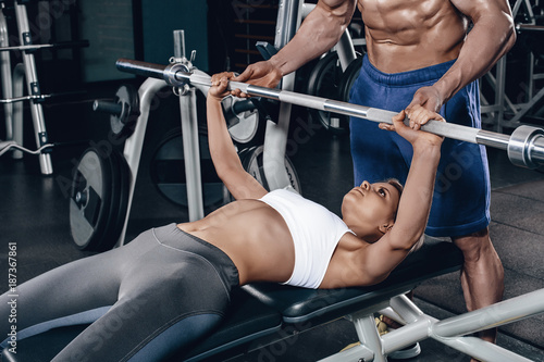 Personal trainer helping a young woman lift a barbell while working out in a gym
