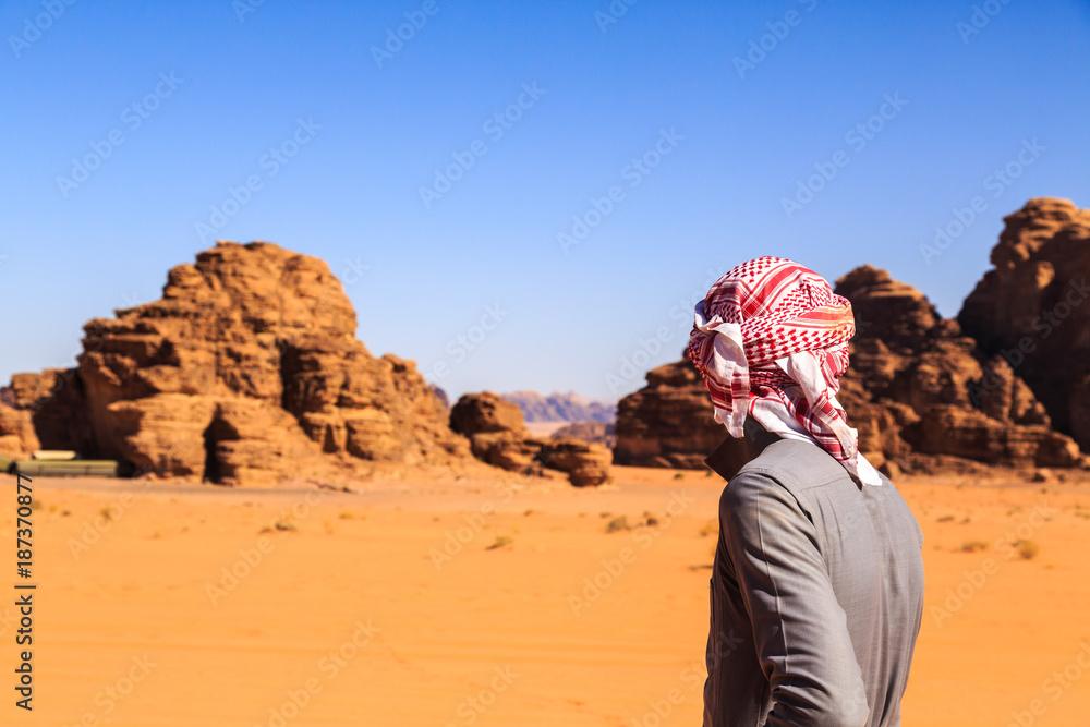 Arab man seen from behind in the Wadi Rum desert in Jordan
