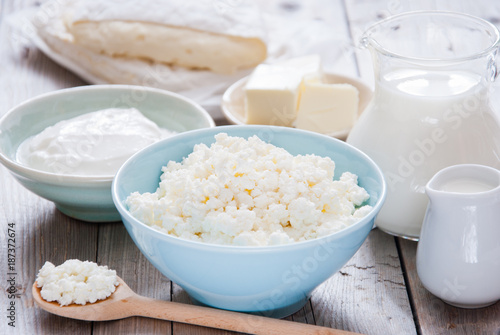 Poster Dairy products Organic Farming Cottage cheese in a blue bowl, sour cream, butter, cheese and milk