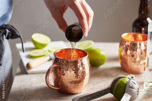 Bartender adding vodka in cocktail.