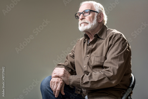 Obraz na plátně Waist up of mature man in glasses sitting on chair