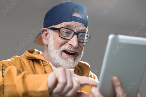 Amused old man in sportswear surfing the internet on tablet Tapéta, Fotótapéta