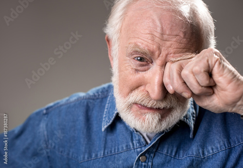 Fototapeta  Portrait of upset old man rubbing his eye while crying