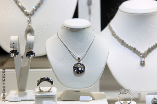 Srebrny naszyjnik, kolczyki i pierścień z diamentami na białych popiersiach w sklepie jubilerskim.