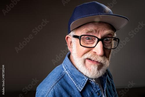 Fotografie, Tablou  Portrait of humorous senior man gazing at camera and cringing