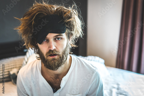 Fototapeta  Guy sit by the bed after a night of drinking alcohol