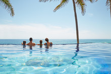 Family With Two Kids On Edge Of Infinity Pool Overlooking Ocean