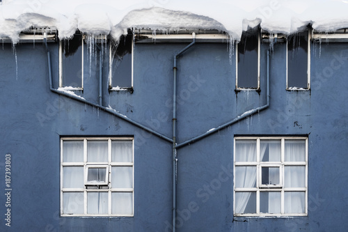 Blue facade of a house in Reykjavik with heavy snow on roof