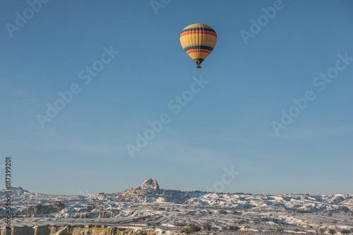 In de dag Ballon colorful hot air balloon above snowcovered city of uchisar, cappadocia, turkey