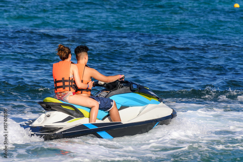 Poster Water Motor sports Young couple riding a jet ski in caribbean sea, wearing safety jackets. Riviera Maya, Mexico
