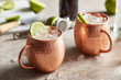 Cups of Moscow mule cocktail with sliced lime.