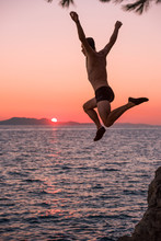 Man Flying In Midair While Jumping In The Sea From High Cliff