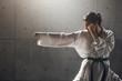 Leinwanddruck Bild - Martial arts Concept. Young woman in kimono practicing karate