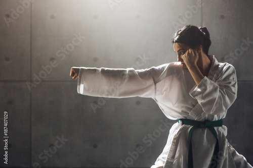 Fotografia Martial arts Concept. Young woman in kimono practicing karate
