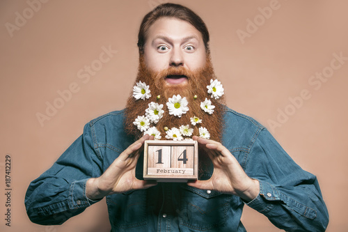 Fotografia, Obraz A man with a beard decorated with flowers. Valentine's Day.