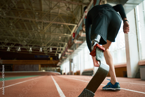 Fotomural  Motivational image of young amputee athlete on start position on running track i