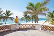 Man on deck of luxury beach resort with glass of wine